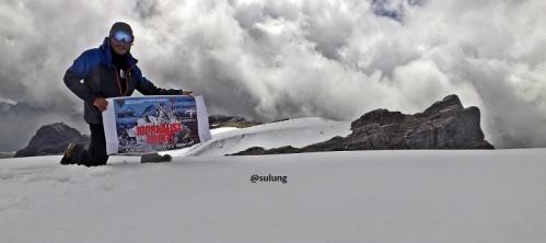 Sukses mendaki seorang diri ke puncak salju Jaya pada 27 Agustus 2015 dengan latar belakang puncak Soemantri, di Pegunungan Tengah, Papua.